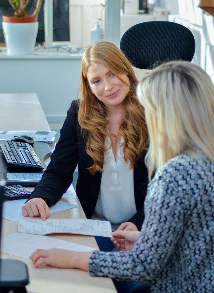 Women discussing paperwork