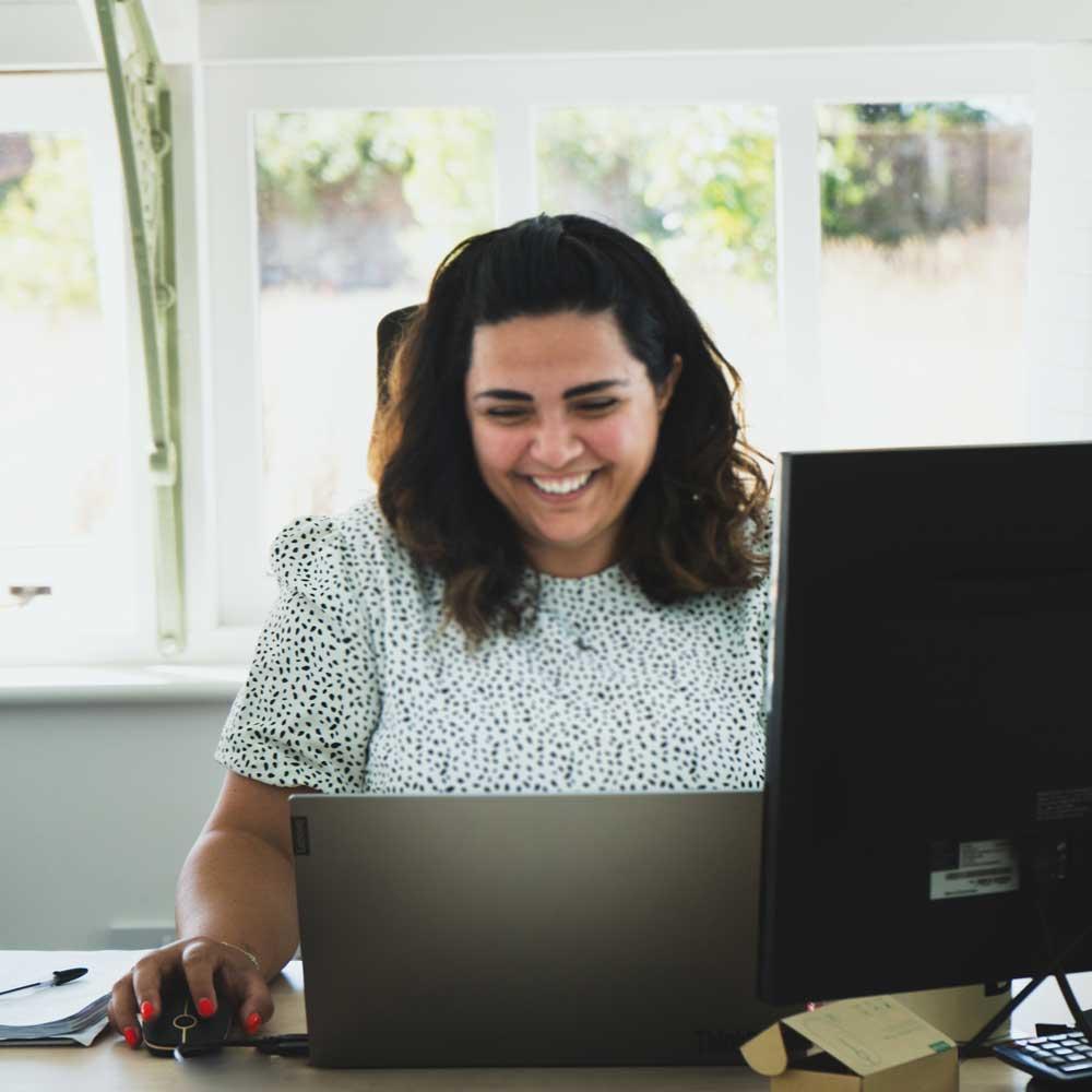 Woman-smiling-at-desk